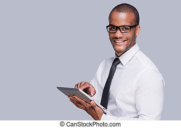 Businessman with digital tablet. Confident young African man...