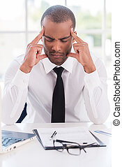 Stressed and tired. Depressed young African man in formalwear holding head in hands and keeping eyes closed while sitting at his working place