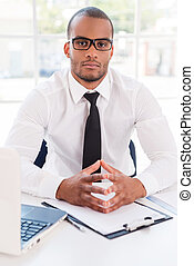 Confident businessman. Confident young African man in shirt and tie looking at camera while sitting at his working place