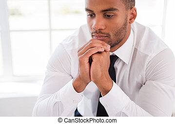 Lost in thoughts. Thoughtful young African man in shirt and...