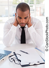 Sick and tired. Depressed young African man in formalwear holding head in hands while sitting at his working place