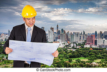 Asian civil engineer in hardhats taking a look at the...