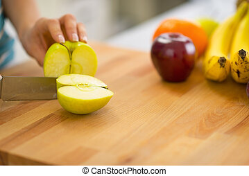 Closeup on young woman cutting apple
