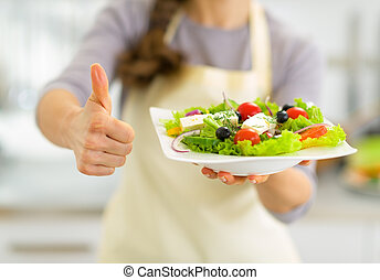 Closeup on young housewife showing greek salad and thumbs up