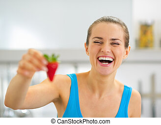 Smiling young woman showing strawberry