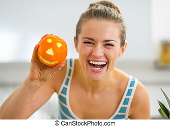 Portrait of happy young woman showing halloween orange