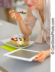 Closeup on happy young woman eating fruit salad and using...