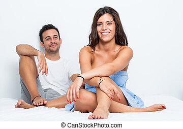Couple on bed in bedroom.