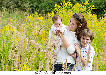 Young mother with two children in a yellow flower field