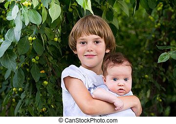Cute boy holding his baby sister outside in a park