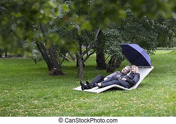 Mature couple relaxing on a deck chair under umbrella