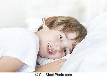 Boy with brown eyes lying on a white pillow