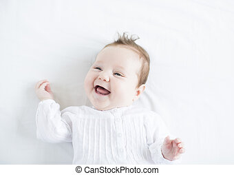 Adorable baby girl in a white dress laughing toothless on a...