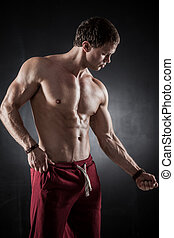 Fitness male model - Handsome athletic man posing on dark...