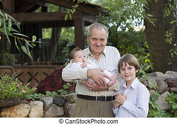 Happy grandfather with his grandchildren in the garden