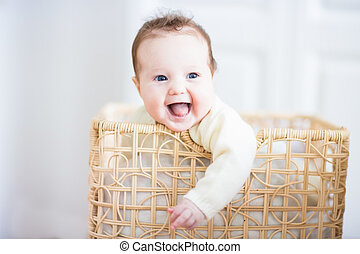 Adorable laughing baby sitting in a laundry basket