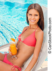 Finding a great place to relax. Top view of beautiful young woman in bikini drinking cocktail and smiling while relaxing in deck chair near the pool