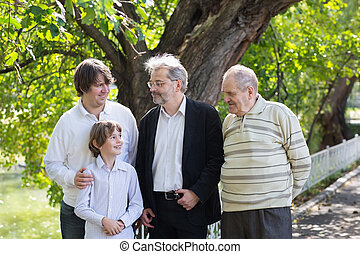 Four generations of men standing in a park looking at each other and laughing
