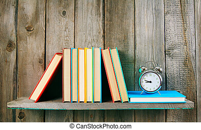 Alarm clock and books on wooden shelf. - Alarm clock and...
