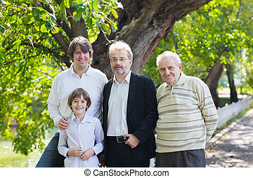 Four generations of men standing in a park