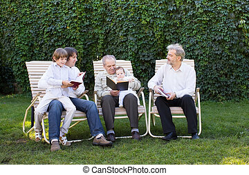 Four generations in the garden, grandfather reading to a baby girl with family members listening