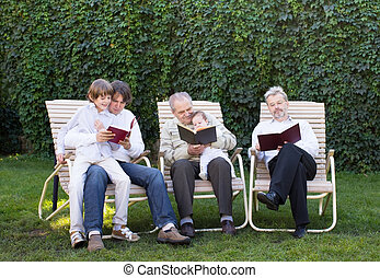 Four generations relaxing in the garden, reading books