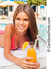 Spending carefree time poolside Beautiful young woman in...