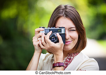 Young woman taking picture with retro camera