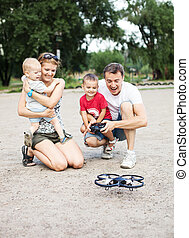 Young family with two boys playing with RC toy - Young...