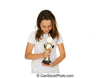 Young girl clasping a sporting trophy closely to her chest...