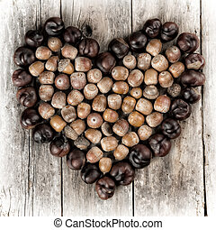 Chestnuts and acorns forming a heart on a wooden background