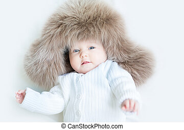 Curious litle baby in a huge fur hat