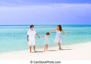 Happy family of three dancing on the beach