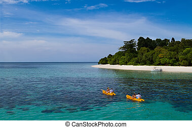Two yellow kayaks next to a tropical exotic island with blue transparent water