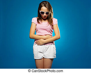 Young girl with a stomach ache clutching her belly with her...