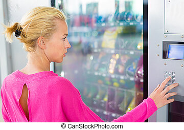 Lady using a modern vending machine - Caucasian woman...