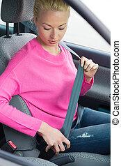 Women driver fastening her seat belt - Safety first. Blonde...