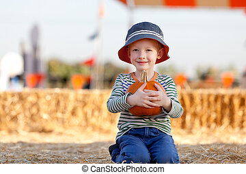kid at pumpkin patch - cheerful little boy at pumpkin patch,...
