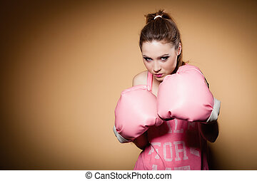 Female boxer wearing big fun pink gloves playing sports -...