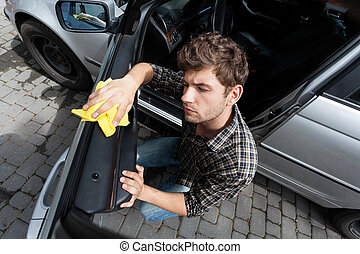 Man cleaning a car - Horizontal view of man cleaning a car