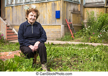 Portrait of old woman near her home.