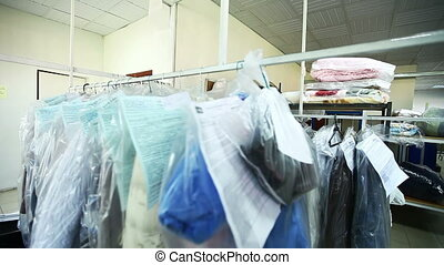 Rack with clean clothes at dry cleaners - View of rack with...