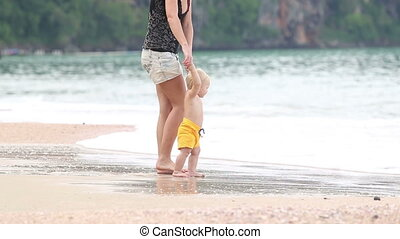 child goes by the handle with his mother on a beach