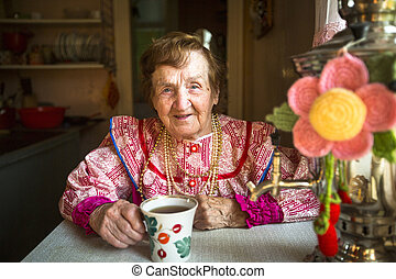 Elderly woman in ethnic clothes drinking tea in his house.
