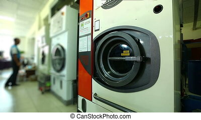 Worker checks washing machines in laundry room - View of...
