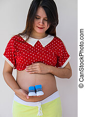 Close-up of a Pregnant Woman  holding Baby Shoes in  Hands. Preg