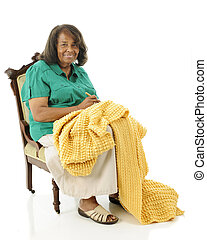 Senior Crocheter - A senior woman happily crocheting her...