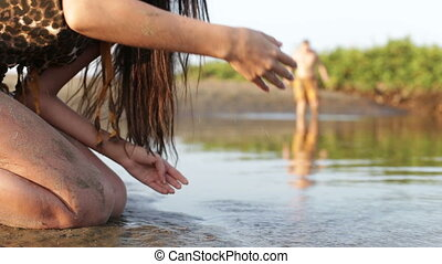 primitive woman drinks water from the pond and on the...