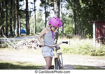 Child with pink bicycle helmet learning to bike