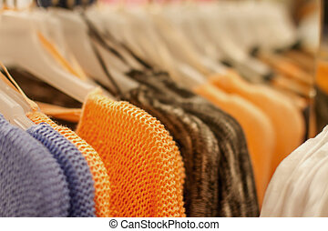 orange sweater on a hanger in the store